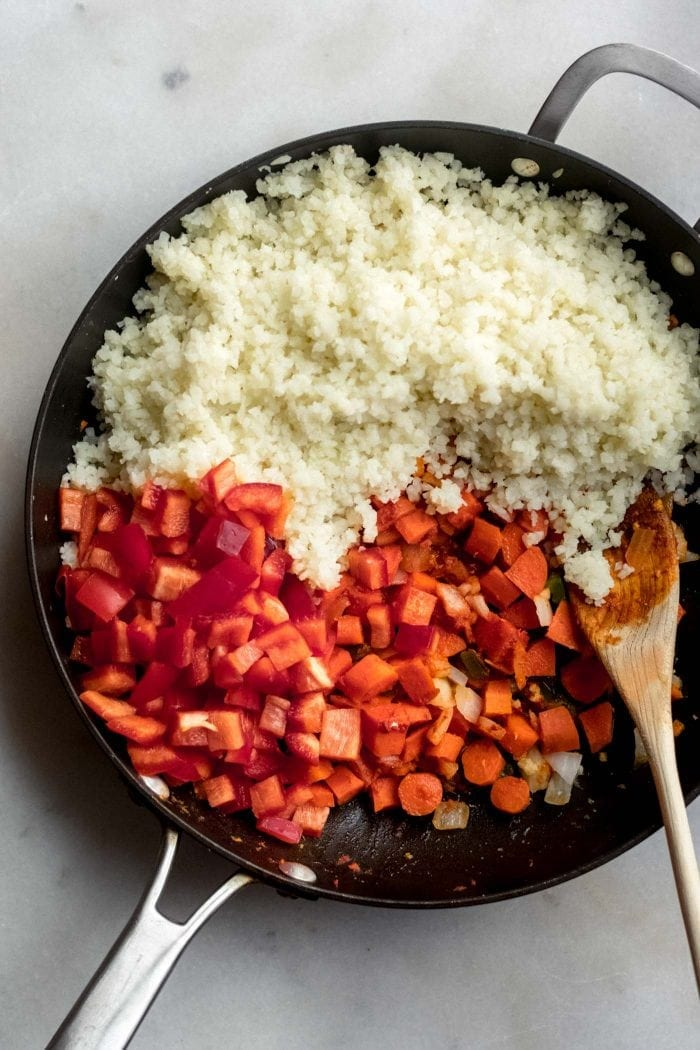 Cauliflower rice with red peppers and cooked carrots in a skillet with a wooden spoon.