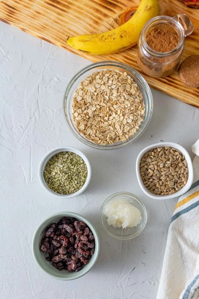 Oats, seeds and raisins in containers on a countertop.
