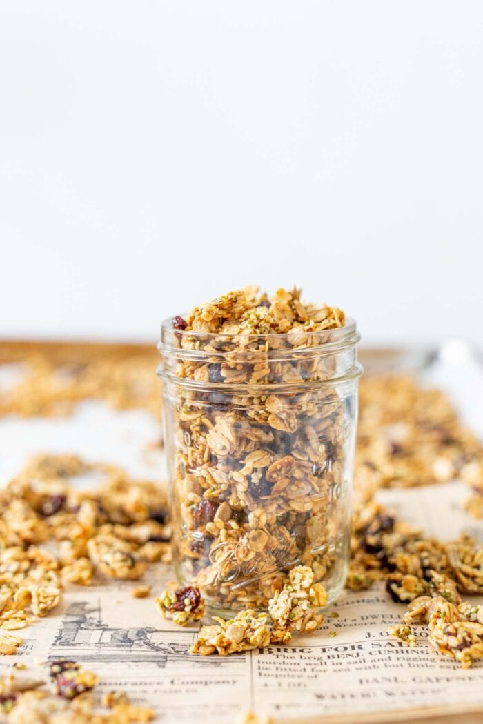 Granola in a glass jar on a baking tray.