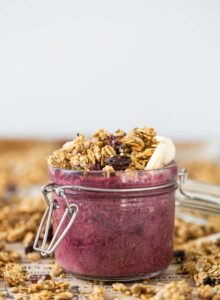 A berry smoothie topped with granola in a jar.