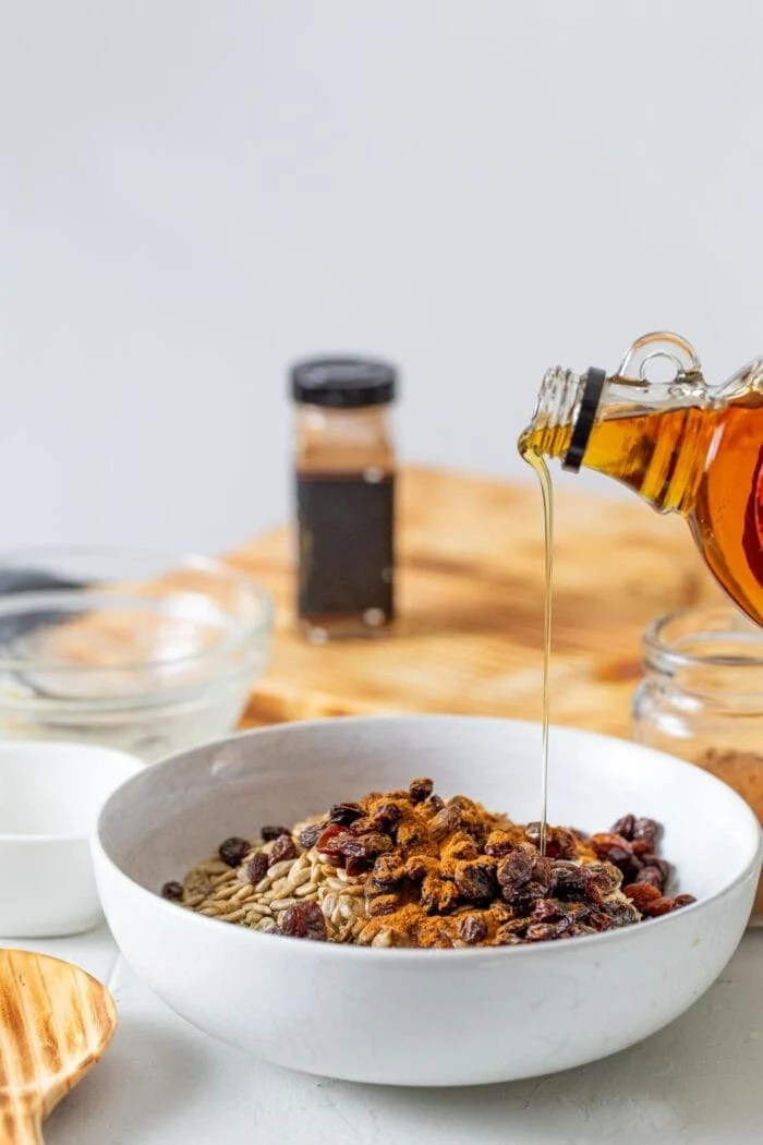 Maple syrup being poured into a mixing bowl of oats, cinnamon and raisin.