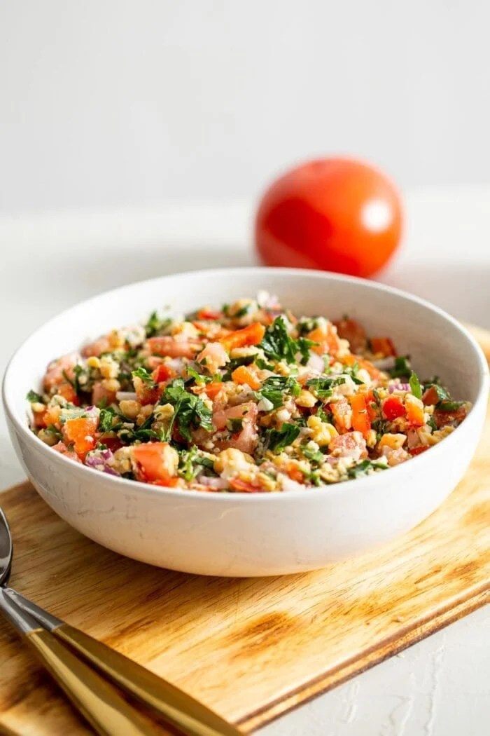 A bowl of tabouleh salad with a tomato in the background.