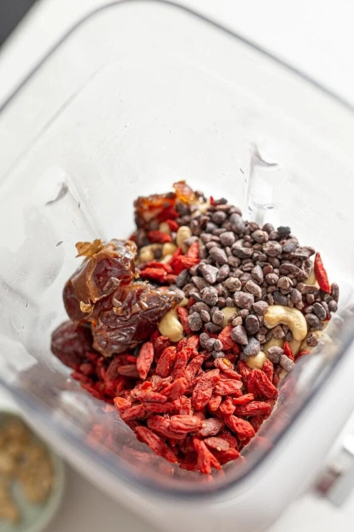 Goji berries, dates, cashews and cacao nibs in a blender.