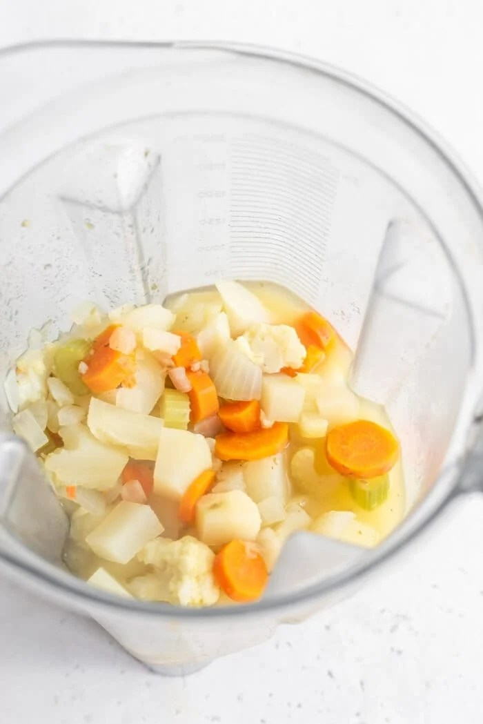 Chopped, cooked vegetables and broth in a Vitamix ready to be blended.