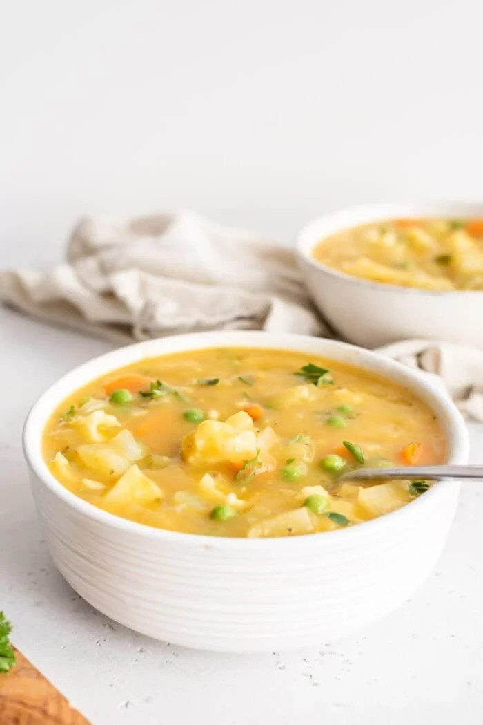Two bowls of chunky cauliflower potato soup against a white background.