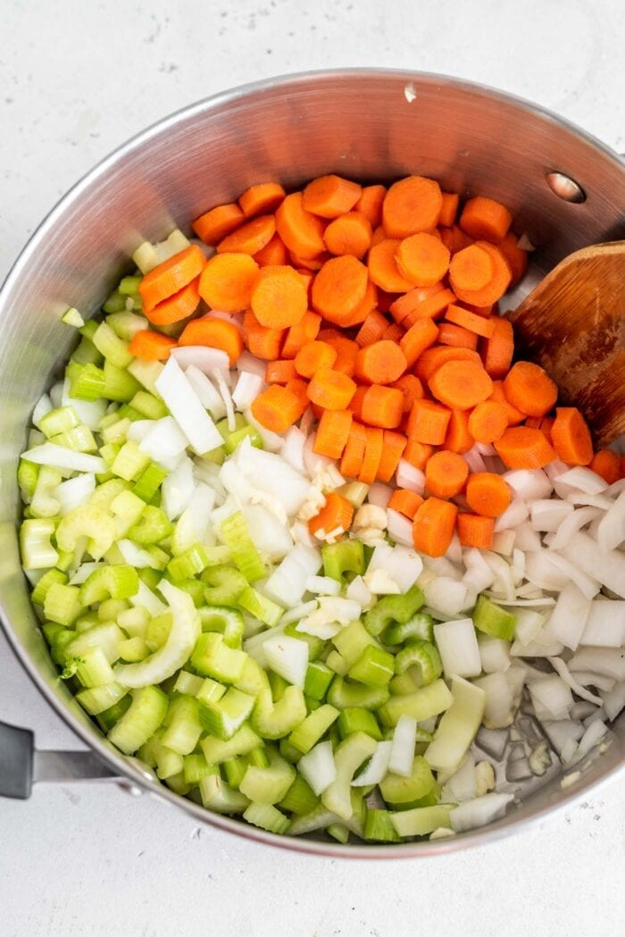 Onions, carrot, celery and garlic in a soup pot with a wooden spoon.