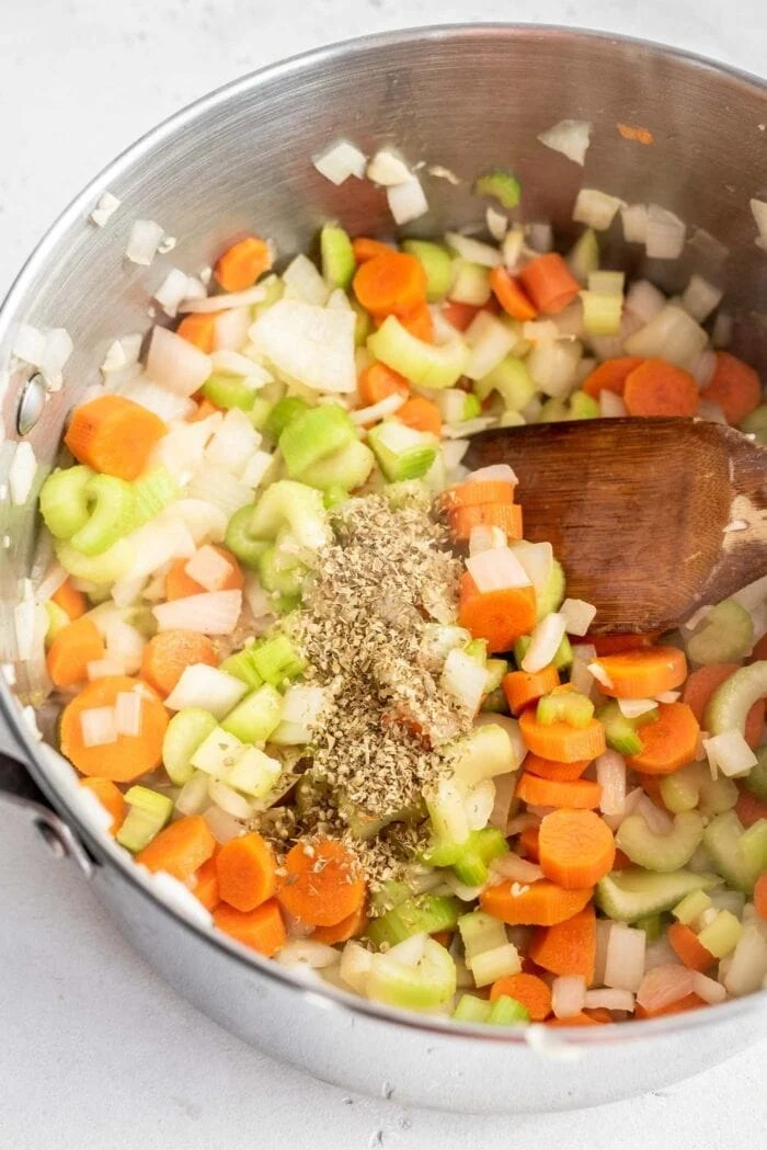 Onions, carrot, celery, dried herbs and garlic in a soup pot with a wooden spoon.