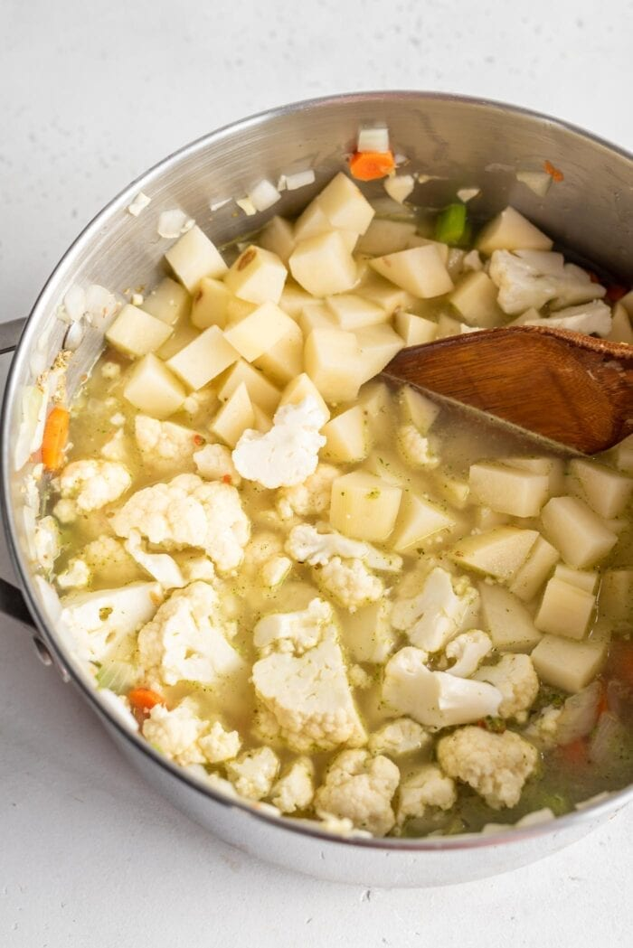 Chopped cauliflower and potato with broth and veggies in a soup pot.