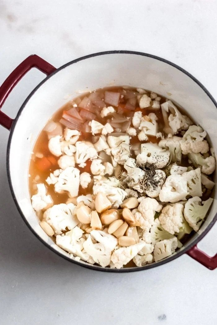 Cauliflower, carrot, onion and roasted garlic in a soup pot.