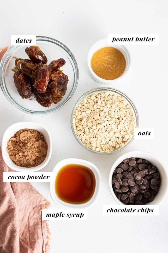 Dates, peanut butter, chocolate and oats in bowls on a counter.