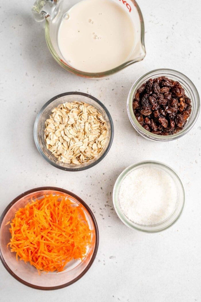 Milk, carrots, coconut, raisins and oats in containers on a white surface.