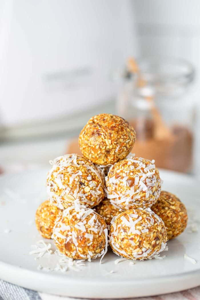 A stack of carrot cake energy balls on a plate.