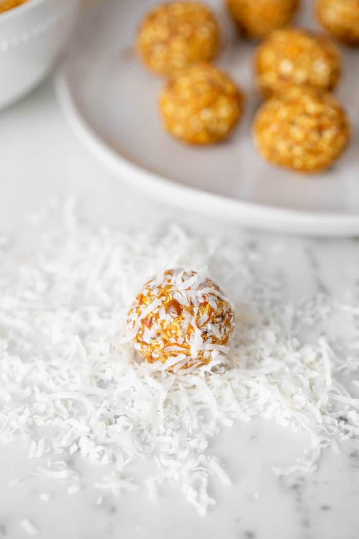 An energy ball being rolled in shredded coconut on a counter top.