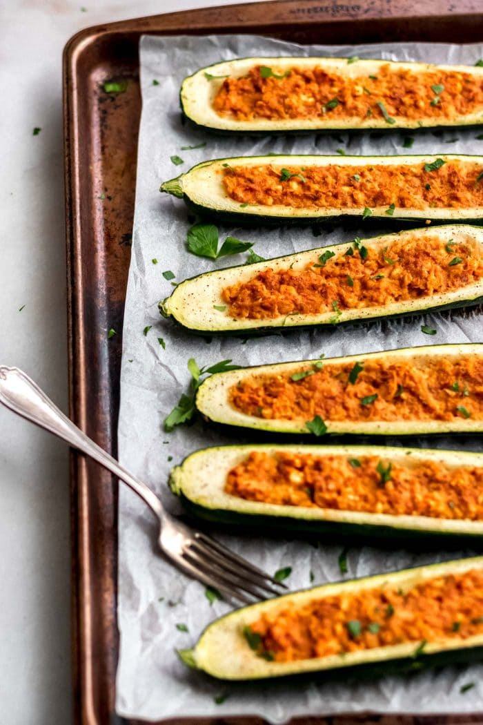 Easy Vegan Chickpea Stuffed Zucchini Boats on a baking tray.