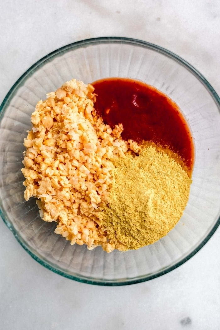 Mashed chickpeas, pasta sauce and nutritional yeast in a bowl.
