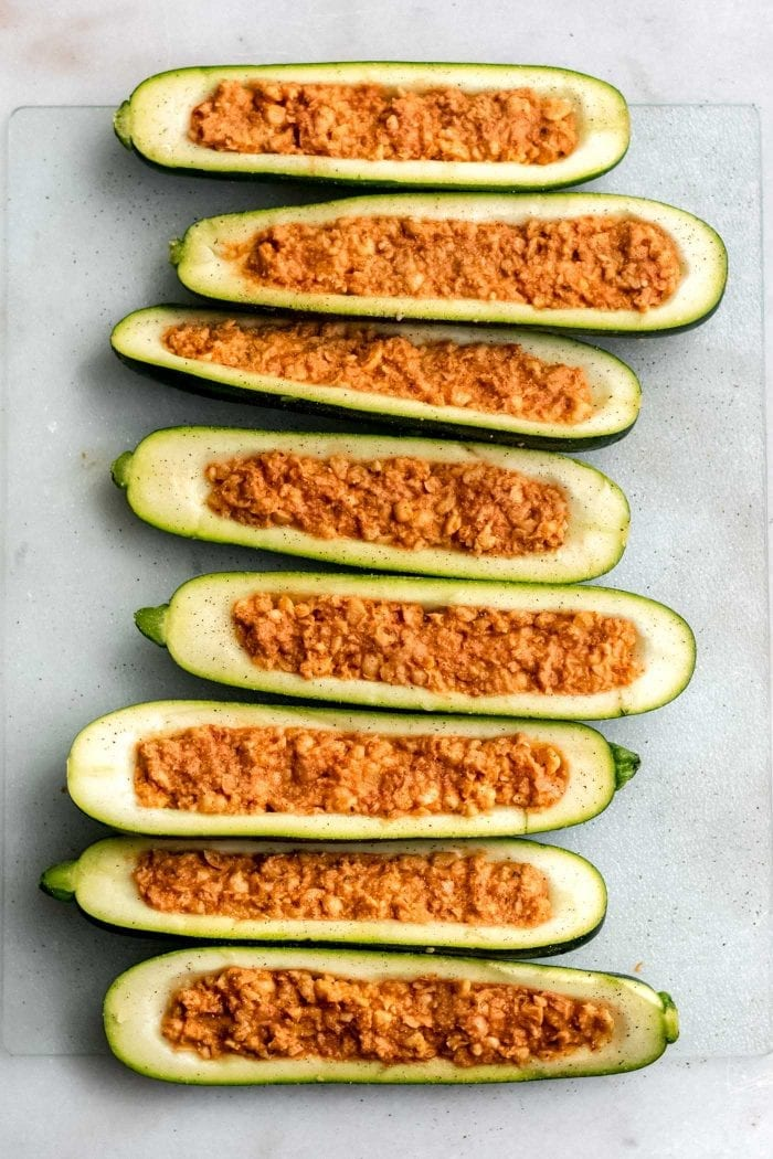Chickpea stuffed zucchini boats ready to go in the oven on a baking tray lined with parchment paper.
