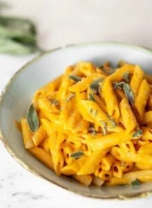 A white bowl of creamy vegan pumpkin pasta.