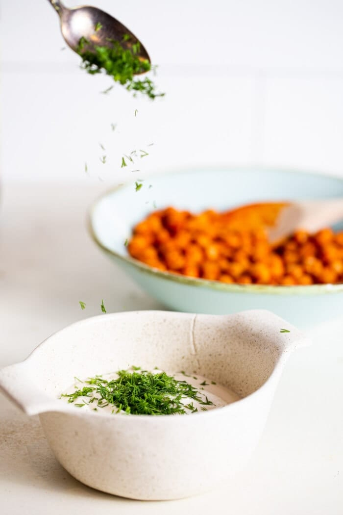 A spoonful of chopped herbs being sprinkled into a small bowl of white dipping sauce.