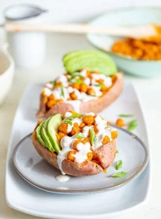 Sweet potato stuffed with buffalo chickpeas and avocado, topped with white sauce.
