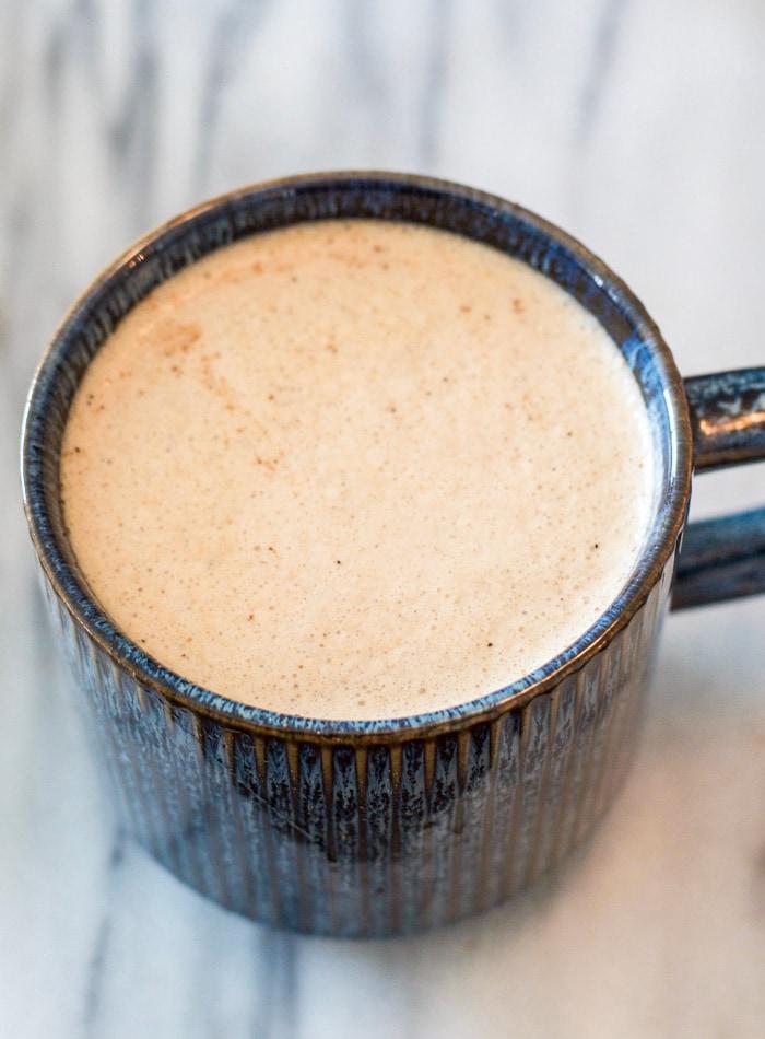 Creamy coffee in a small blue mug.