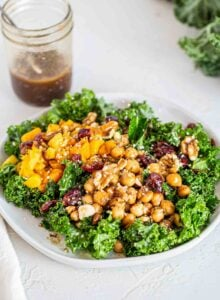 A kale salad topped with squash, chickpeas, cranberries, hemp seeds and walnuts.