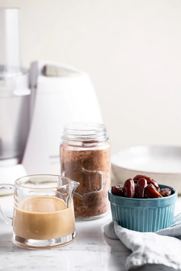Containers of tahini, cacao powder and dates sitting in front of a food processor.