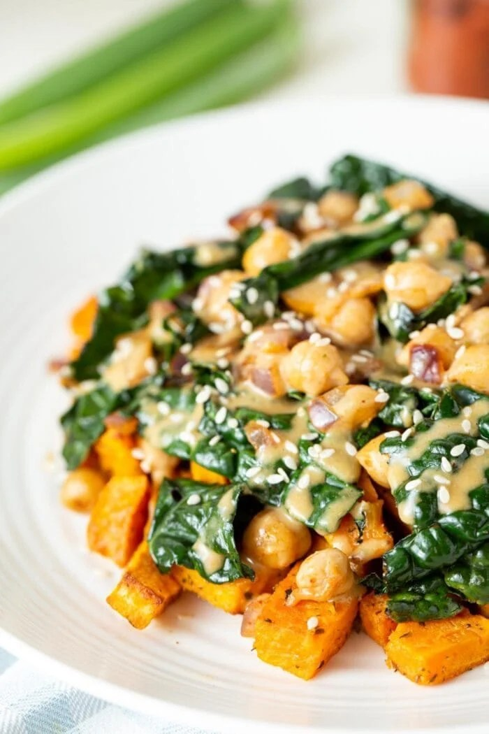 A plate of vegan kale chickpea stir fry with miso peanut sauce.