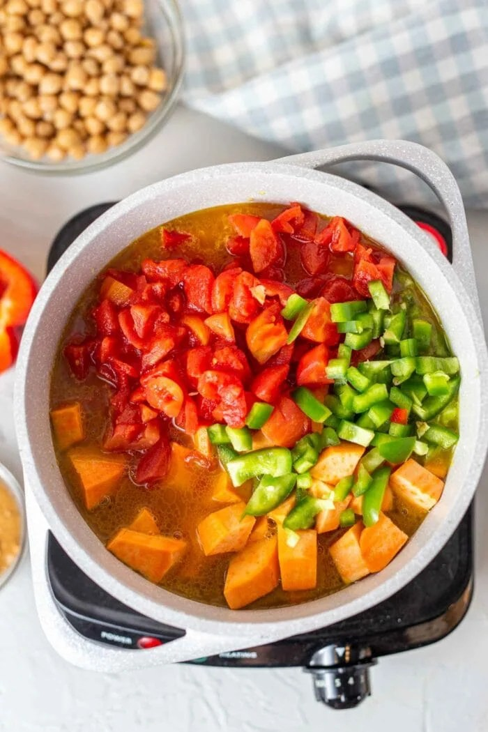 A large pot of sweet potato, tomato and bell peppers.