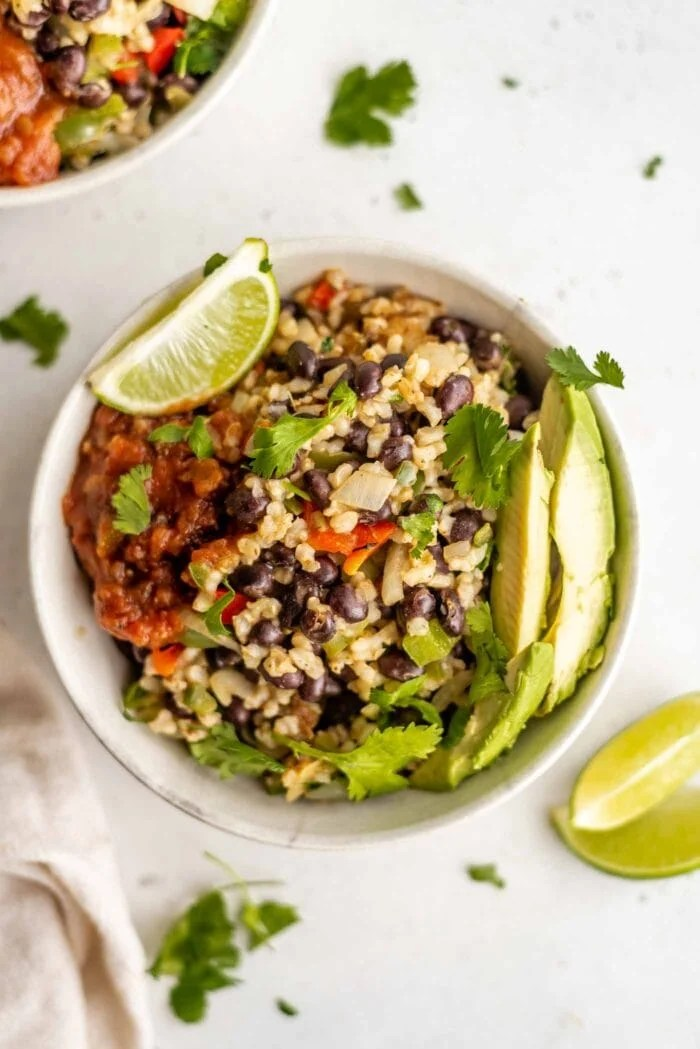 A bowl of rice and beans topped with avocado and salsa.
