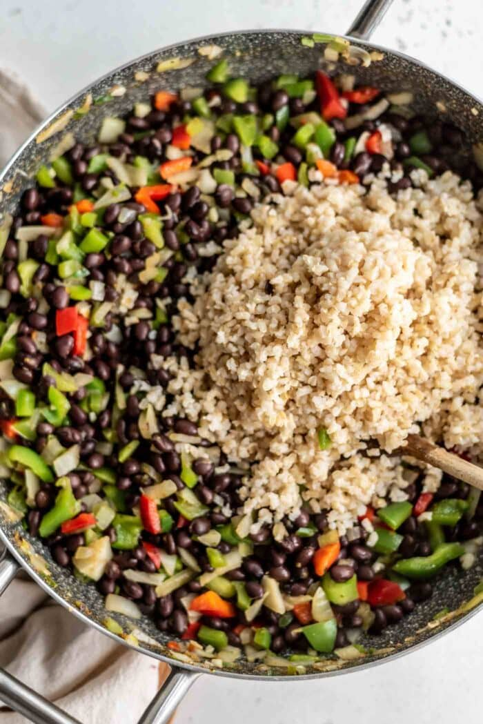A large scoop of brown rice being added to a skillet of beans and veggies.