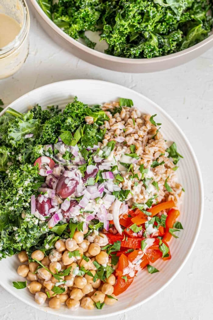A farro salad with chickpeas, kale, roasted red peppers, olives and red onion.