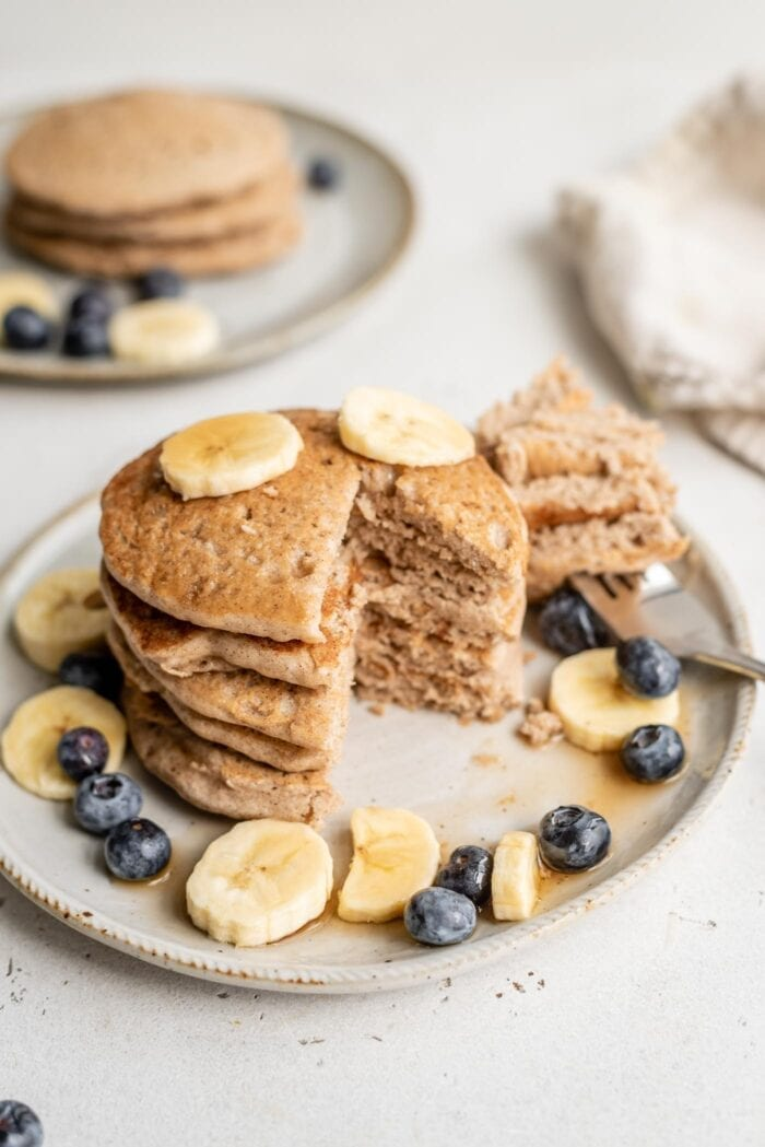 A sliced stack of blueberry and banana topped pancakes on a plate.