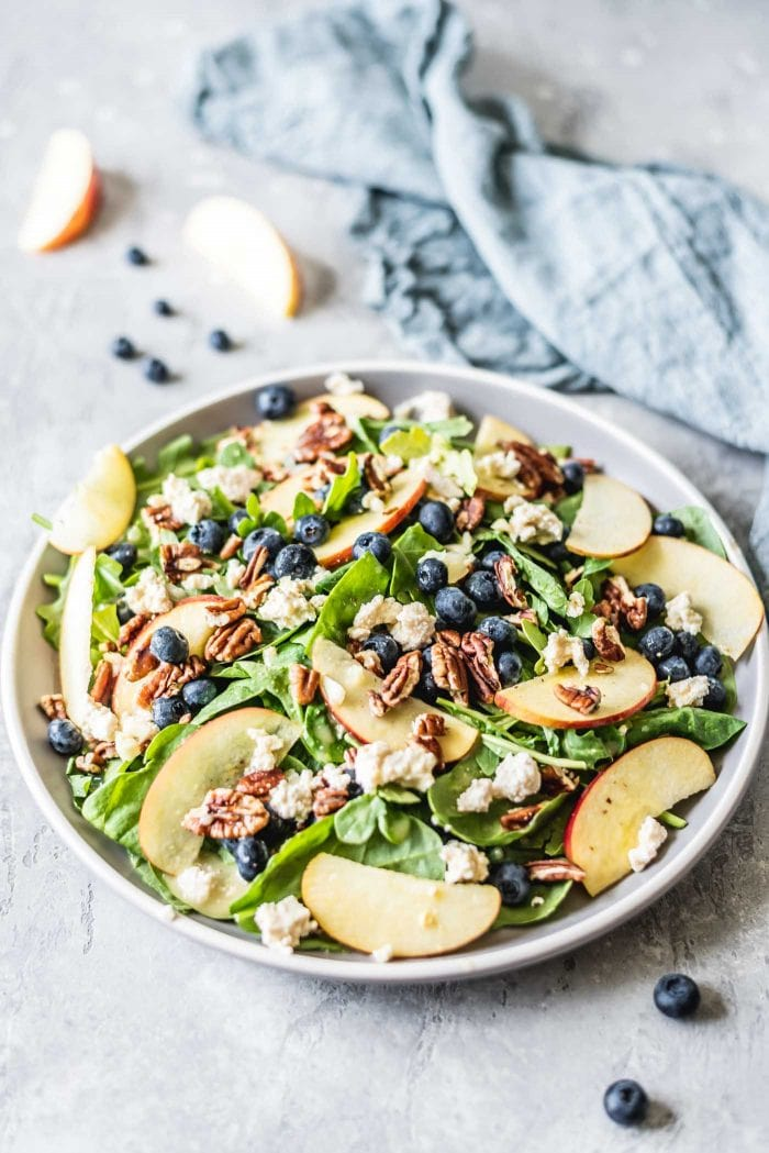 Spinach salad on a grey plate with blueberries, pecans, apple and tofu feta.