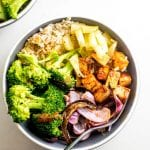 Bowl with tofu, broccoli, brown rice and roasted red onions.