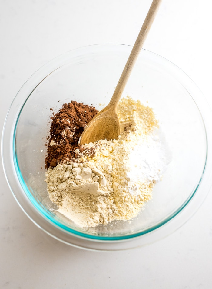 Chickpea flour, cocoa powder and baking powder in a glass mixing bowl.