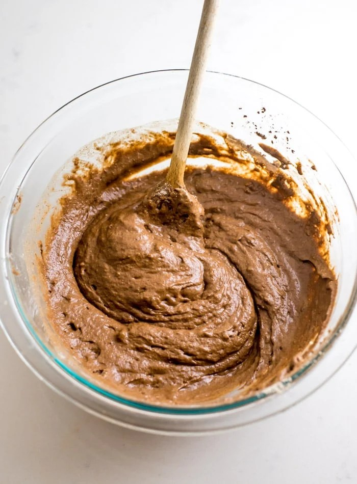 Raw chocolate pancake batter in a glass mixing bowl.