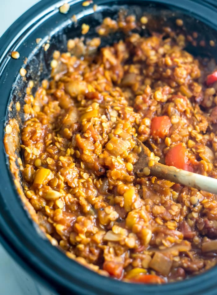 Red lentil and bell pepper chili cooking in a slow cooker.