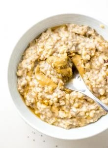 Bowl of banana oatmeal topped with peanut butter.