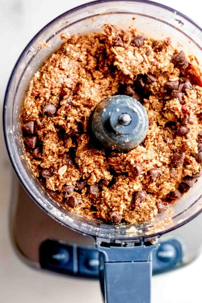 Overhead image of a thick dough with chocolate chips in a food processor.