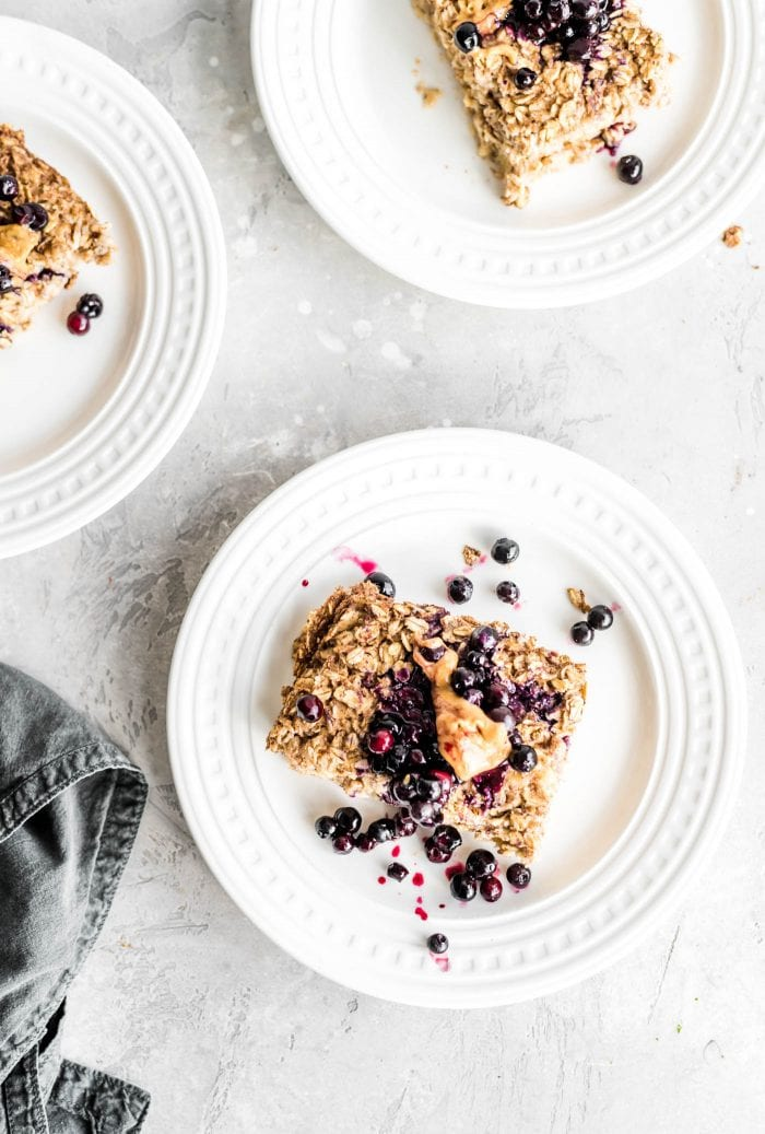 Baked oatmeal with blueberries and peanut butter on a small white plate.