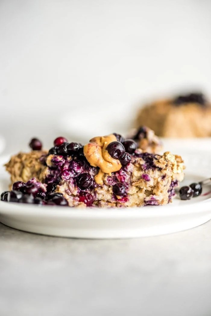 Banana baked oatmeal on a small white plate topped with berries and peanut butter.