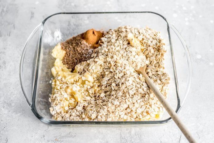 Rolled oats, ground flax, cinnamon and mashed banana with a wooden spoon in a glass baking dish.