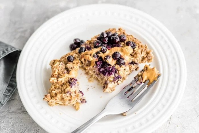 Healthy Baked Oat Recipe on a small white plate with a fork, peanut butter and fresh blueberries.