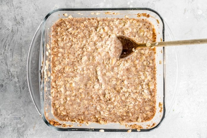 Mixed baked oatmeal ingredients in a glass baking dish before going in the oven.