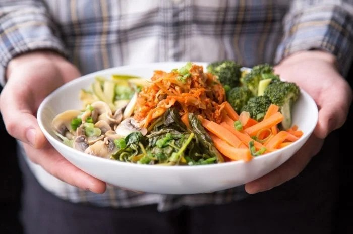 A person holding a bowl with carrots, kimchi, broccoli, greens and mushrooms.