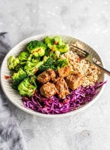 Baked tempeh, brown rice, broccoli and red cabbage in a bowl with Sriracha sauce.