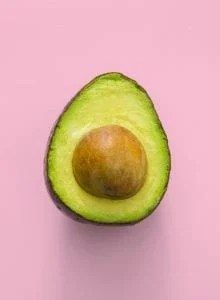 Ripe cut avocado on a pink background.