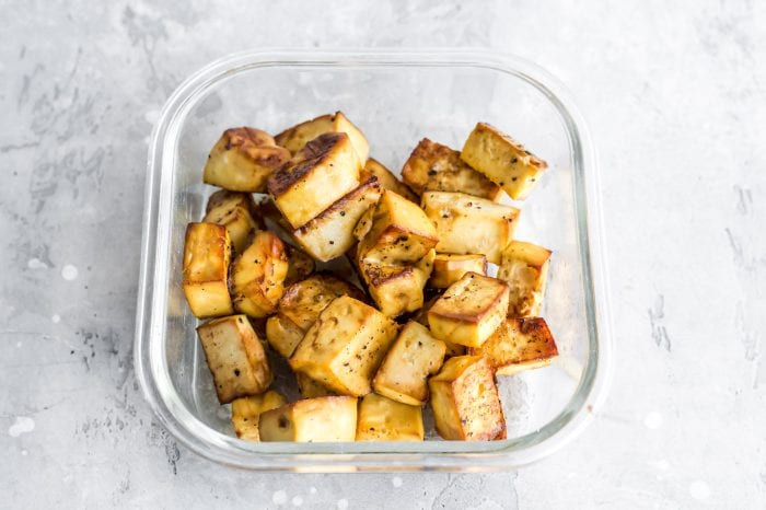 Baked tofu in a glass container for vegan meal prep.