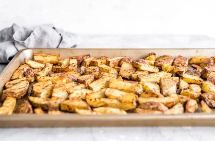 Chopped roasted potatoes on a baking tray.