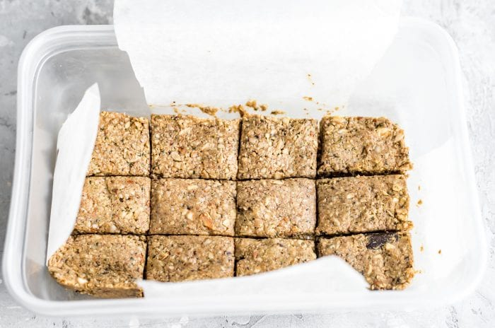 Cut almond hemp energy bars in a Tupperwear container with parchment paper.